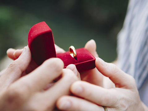Couple holding a ring to qualify for sponsor partner visa